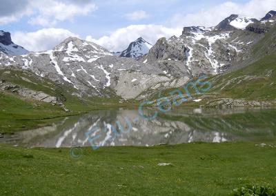 Lac sur les hauteurs entourée de pics rocheux enneigés