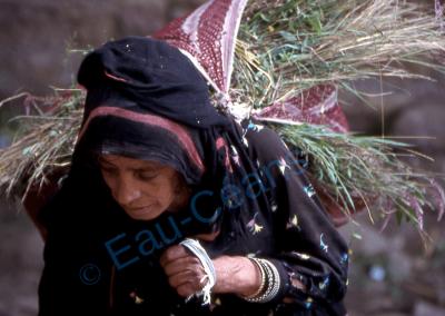 Une femme remonte de la vallée chargée de nourriture pour les animaux