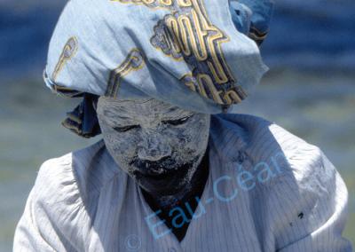 Pêcheuse mozambicaine au visage recouvert d'un masque fabriqué avec un suc végétal